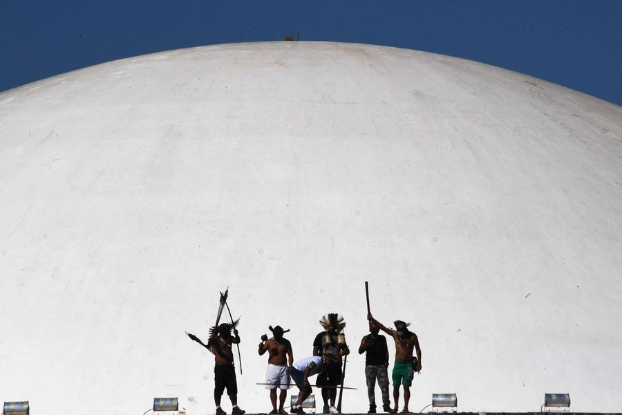 Half a dozen indigenous people protest in front of a large white dome.