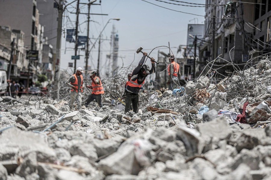 Several people in safety vests work in a pile of rubble in a street.