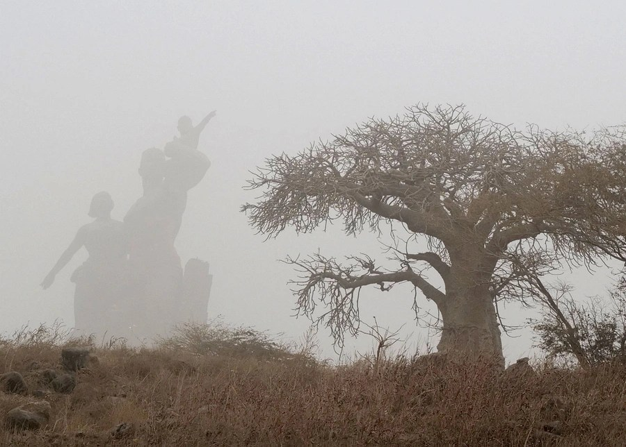 Trees and a large statue are seen in thick fog.