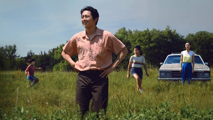 The Yi family stands in a field in front of their car