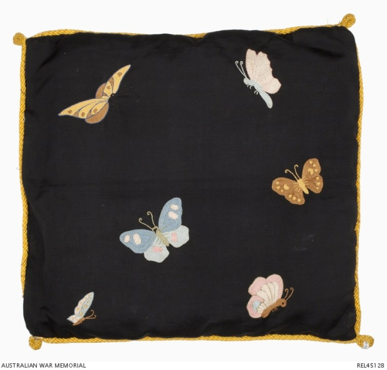 Six multi-coloured butterflies embroidered on the back of the cushion cover decorated with the Australian coat of arms by Lance Corporal Alfred Briggs (Albert Biggs), 20 Battalion, AIF. Credit: Australian War Memorial/The Conversation
