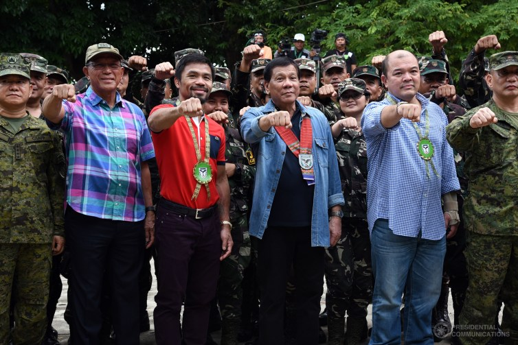 Rodrigo Duterte poses with the Philippines military and boxer and senator Manny Pacquiao in 2017. Credit: Rene Lumawag/Republic of the Philippines Presidential Communications Office