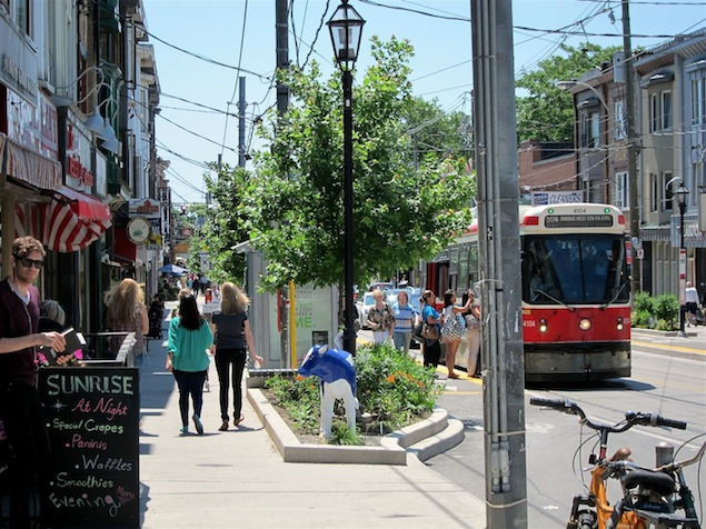 Beautiful day on Roncesvalles avenue showing passengers boarding streetcar, trees, plant beds and shoppers.