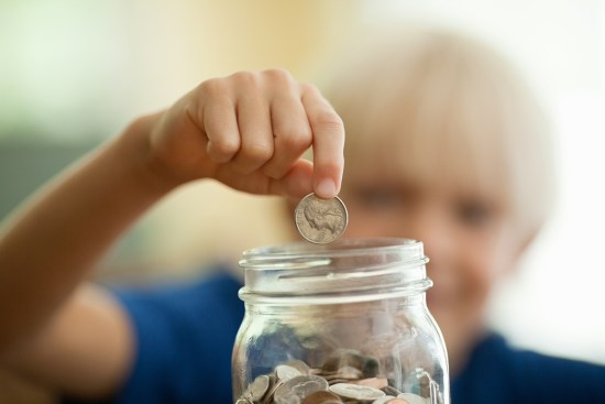 Little boy saving coin in a money jar
