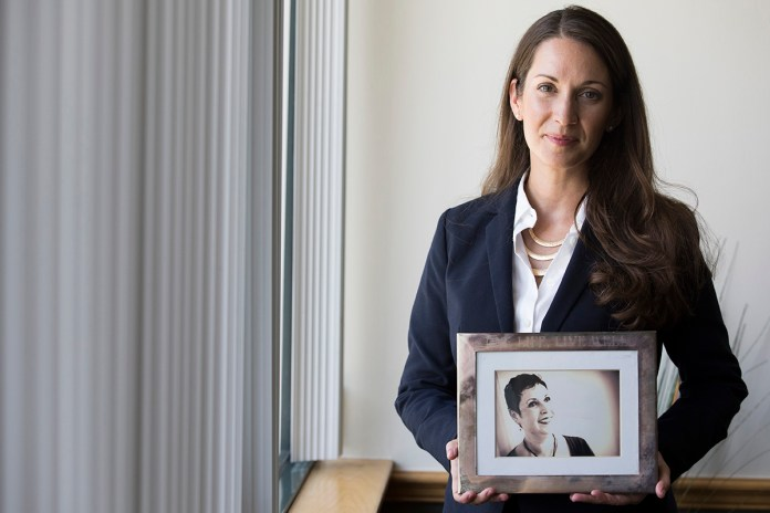 A woman holds a photo of her mother who passed away from brain cancer.