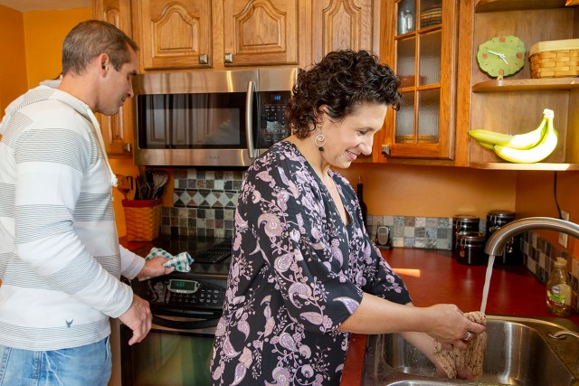 A husband and wife work together in their kitchen.