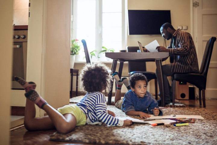 A man looks over his finances as his children draw.