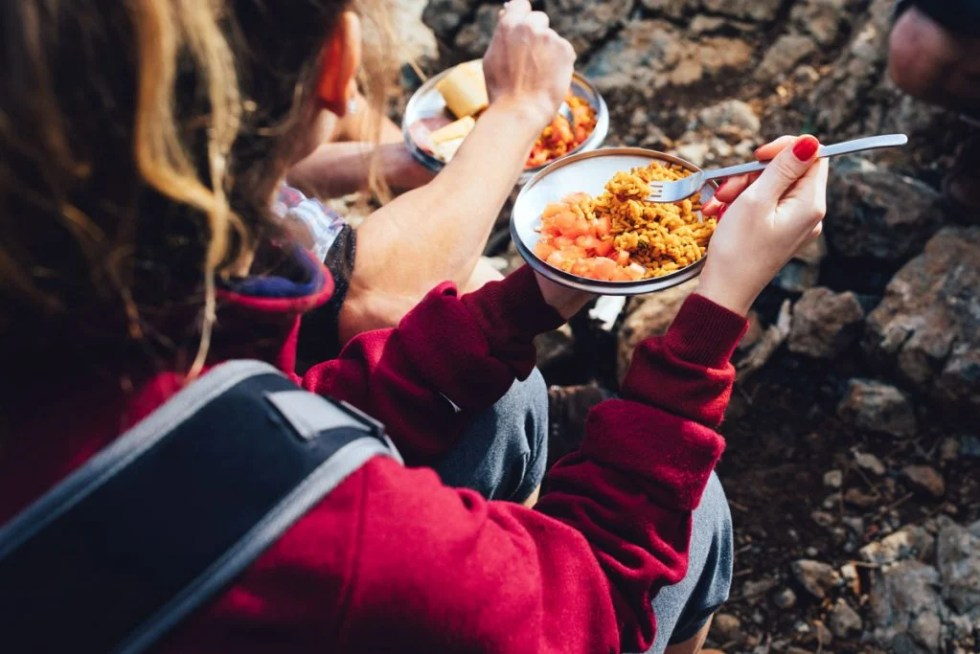 People eat food during a hike.