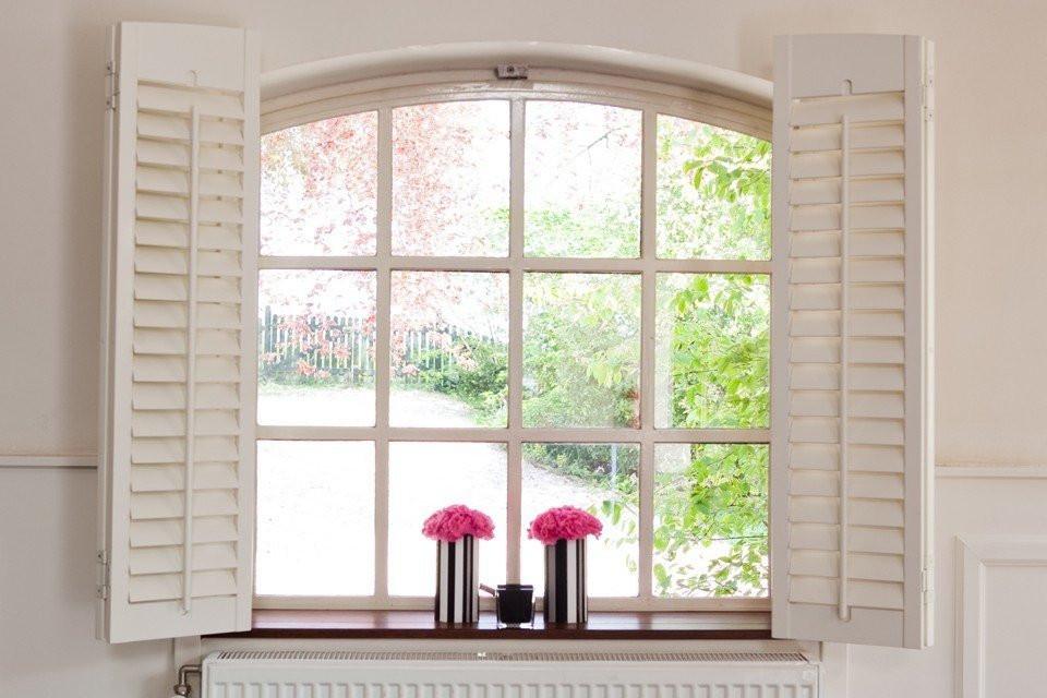roze pioenrozen in strakke vaasjes bij groot raam