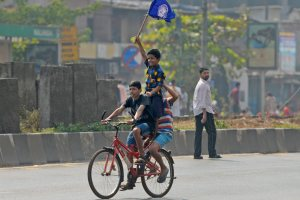 Boys carry a flag while riding a bicycle across a deserted road after Dalits called for Maharashtra bandh to protest the Bhima Koregaon violence, in Mumbai on Wednesday. Credit: PTI/Shashank Parade
