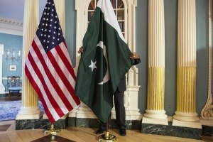 A State Department contractor adjust a Pakistan national flag before a meeting between US Secretary of State John Kerry and Pakistan's Interior Minister Chaudhry Nisar Ali Khan on the sidelines of the White House Summit on Countering Violent Extremism at the State Department in Washington February 19, 2015. Credit: Reuters/Joshua Roberts