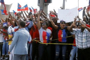 Demonstrators hold up Haitian flags and shout as the motorcade of US President Donald Trump passes in West Palm Beach, Florida, US, January 15, 2018. Credit: Reuters/Kevin Lamarque