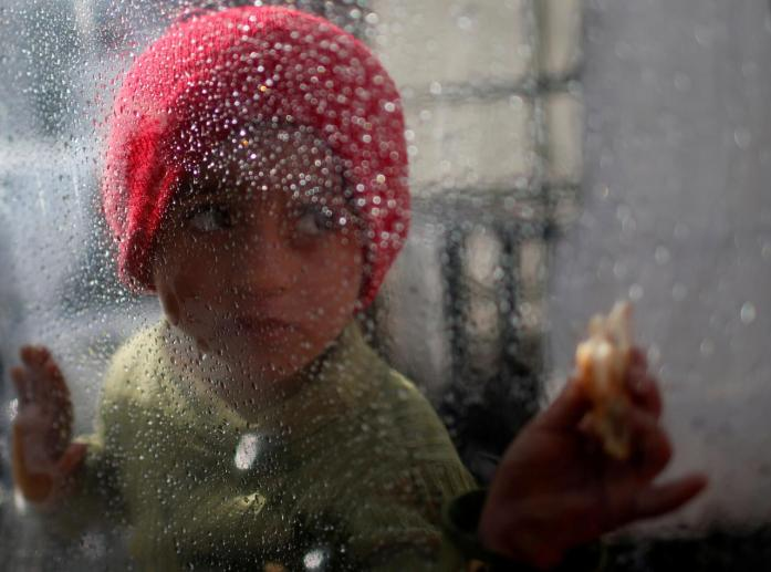 A Palestinian girl looks through a plastic sheet as raindrops are seen, outside her family's house in Al-Shati refugee camp in Gaza City January 17, 2018. Credit: Reuters/Mohammed Salem