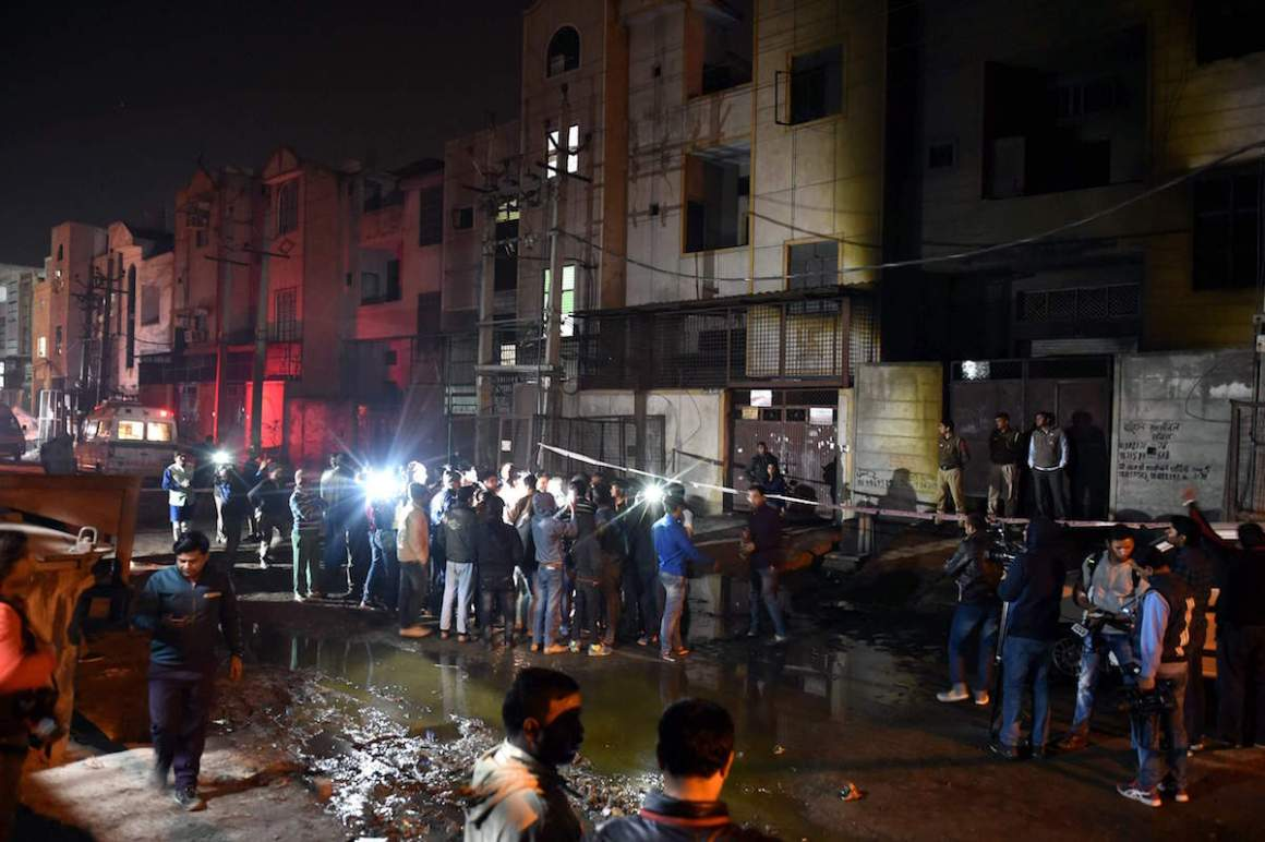 Fire fighters and media outside the two-storey cracker factory which caught fire in north Delhi's Bawana Industrial Area on Saturday. Credit: PTI