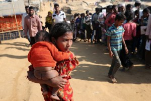 A Rohingya girl carries a child in Kutupalong refugee camp in Cox's Bazar, Bangladesh, January 21, 2018. Credit: