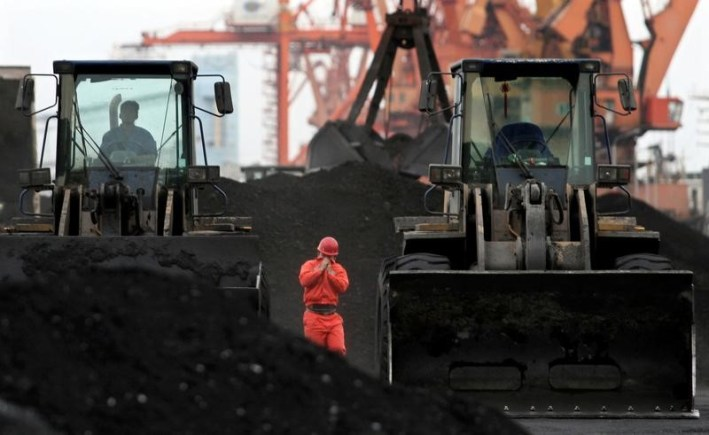 An employee walks between front-end loaders which are used to move coal imported from North Korea at Dandong port in the Chinese border city of Dandong, Liaoning province December 7, 2010. Credit: Reuters/Stringer