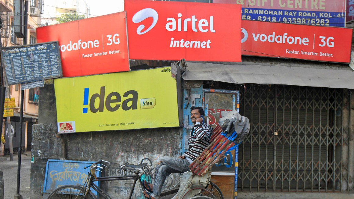A rickshaw puller speaks on his mobile phone as he waits for customers in front of advertisement billboards belonging to telecom companies in Kolkata February 3, 2014. Credit: Reuters/Rupak De Chowdhuri