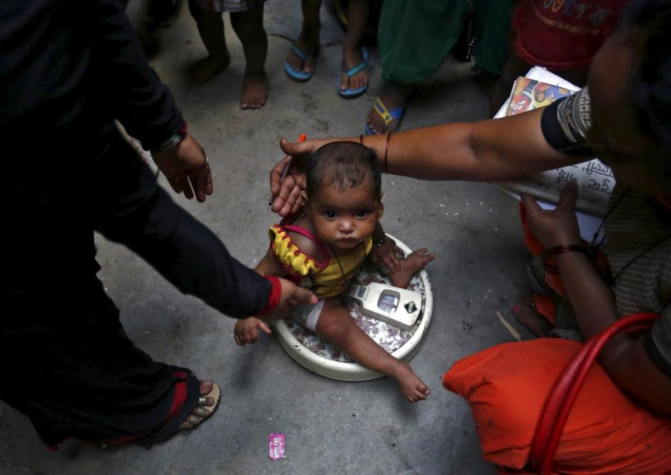 A health worker (R) weighs a child under a government program in New Delhi, India, May 7, 2015. Credit: Reuters/Anindito Mukherjee