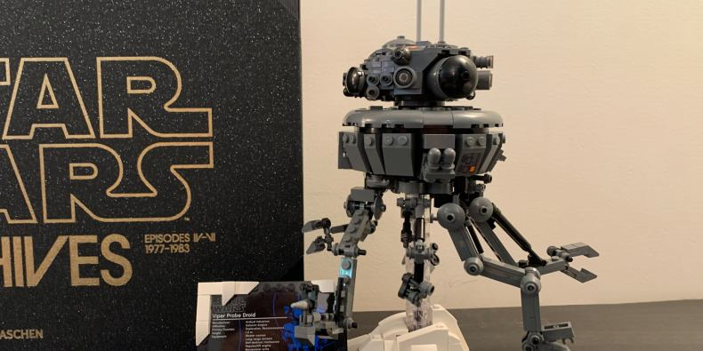 The lego imperial probe droid from star wars, mounted on a stand with an information plaque.