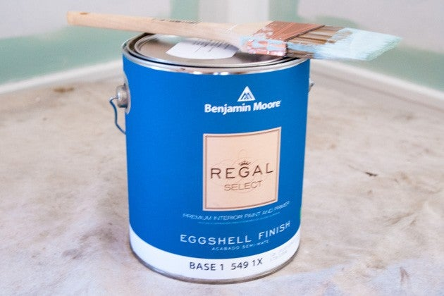 Close Up Of Regal Select Paint Can With Brush Balanced On Top