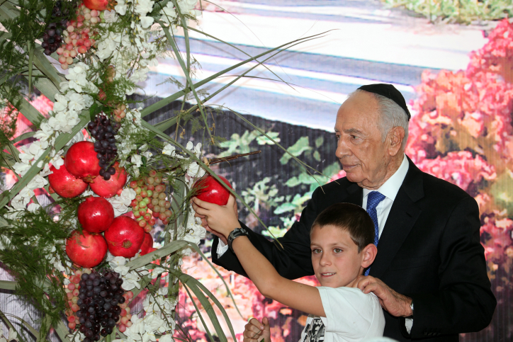 President Shimon Peres welcomes children to his wooden sukkah, September 2012 (photo credit: Yoav Ari Dudkevitch/Flash90)