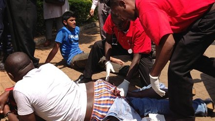 An injured man is treated outside an upscale shopping mall in Nairobi, Kenya, after an attack there left at least 15 people dead, Saturday Sept 21, 2013 (AP Photo/ Jason Straziuso)