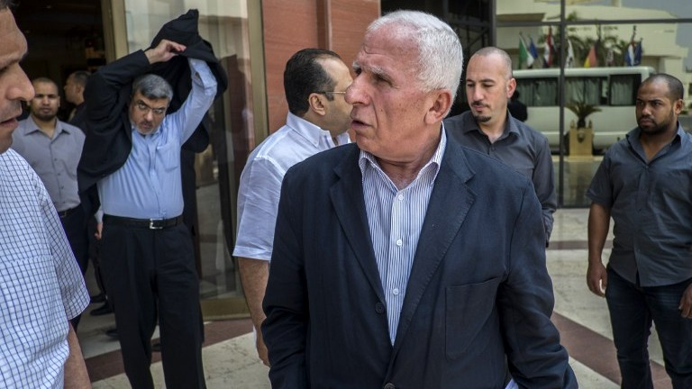 Palestinian Fatah delegation chief Azzam al-Ahmed, center, and members of the delegation leave the hotel where the negotiations are taking place with Egyptian intelligence mediators aimed at brokering an end to the Gaza conflict on August 12, 2014 in the Egyptian capital, Cairo. (photo credit: AFP/KHALED DESOUKI)