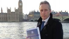 Le député Ian Pasley du Parti unioniste démocrate tenant dans ses bras le rapport parlementaire sur l'antisémitisme (Crédit : Autorisation)