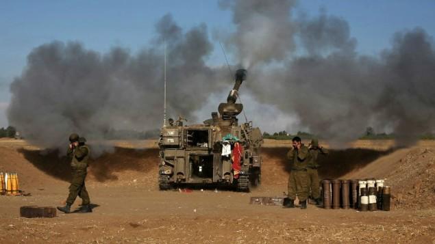 Un tank d'artillerie de 155 mm, placé près de la frontière israélienne avec la bande de Gaza, tire un projectile vers des cibles de l'enclave palestinienne, le 17 juillet 2014. (Crédit photo: AFP / Menahem Kahana)