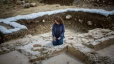 Annette Nagar de l'Autorité des Antiquités regarde les fonts baptismaux de l'église de l'époque byzantine découverte à Abu Ghosh lors des travaux d'agrandissement et de modernisation de l'autoroute Jérusalem-Tel Aviv en juin 2015 (Yonatan Sindel / Flash90)