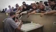 Des Palestiniens se rassemblent à la frontière de Rafah, dans le sud de la bande de Gaza, où ils attendent l'autorisation d'entrer en Egypte, le 12 juin 2015. [Flash90 / AAED Tayeh]