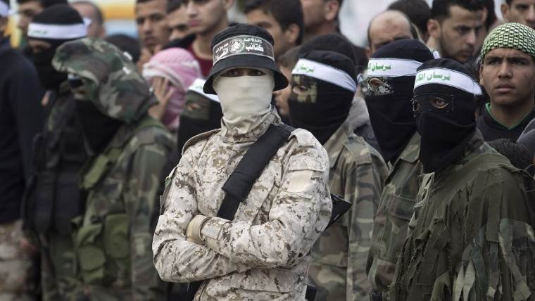 Gunmen from the Izz al-Din al-Qassam Brigades, the armed wing of Hamas, stand guard during a parade marking the ruling Islamist terror movement's 28th birthday on December 11, 2015, in Khan Yunis, in the southern Gaza Strip. (Said Khatib/AFP)