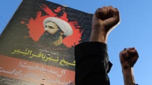 Les manifestants iraniens soulèvant leurs poings en face d'un portrait de l'éminent dignitaire religieux chiite Nimr al-Nimr pendant une manifestation contre son exécution par les autorités saoudiennes, le 3 janvier 2016, devant l'ambassade d'Arabie Saoudite à Téhéran (Crédit : AFP PHOTO / ATTA KENARE)
