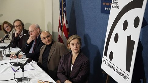 Members of the Bulletin of the Atomic Scientists sit after unveiling the 'Doomsday Clock' that remains at three minutes to midnight, Tuesday, Jan. 26, 2016 (AP Photo/Alex Brandon)