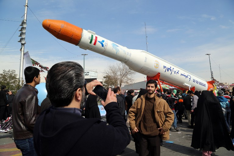 Iranians take photos of the Simorgh satellite rocket during celebrations to mark the 37th anniversary of the Islamic Revolution, in Teheran, February 11, 2016. (AFP/Atta Kenare)
