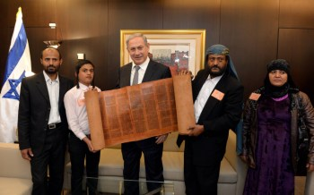 Israeli Prime Minister Benjamin Netanyahu holds an 500 hundred-year-old Torah scroll as he poses for a picture with some of the Yemenite Jews who were brought to Israel as part of a secret rescue operation, at the Knesset on March 21, 2016. (Haim Zach/GPO)