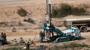 Sur cette photo d'illustration du 10 février 2016, des soldats israéliens surveillent une machine permettant de creuser des trous dans le sol côté israélien de la frontière avec la bande de Gaza pour détecter des tunnels utilisés par des groupes terroristes palestiniens qui prévoient d'attaquer Israël. (Crédit : AFP PHOTO/MENAHEM KAHANA)