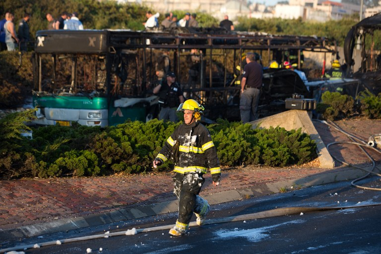 An Israeli fireman walks past the remains of a burnt-out bus after extinguishing the flames following an explosion in Jerusalem on April 18, 2016. (AFP PHOTO / MENAHEM KAHANA)