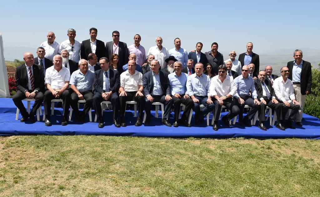 El primer ministro israelí, Benjamin Netanyahu, posa para una foto de grupo con su gobierno en la reunión semanal del gabinete, que tuvo lugar en los Altos del Golán, el 17 de abril de 2016. (Effi Sharir / POOL)