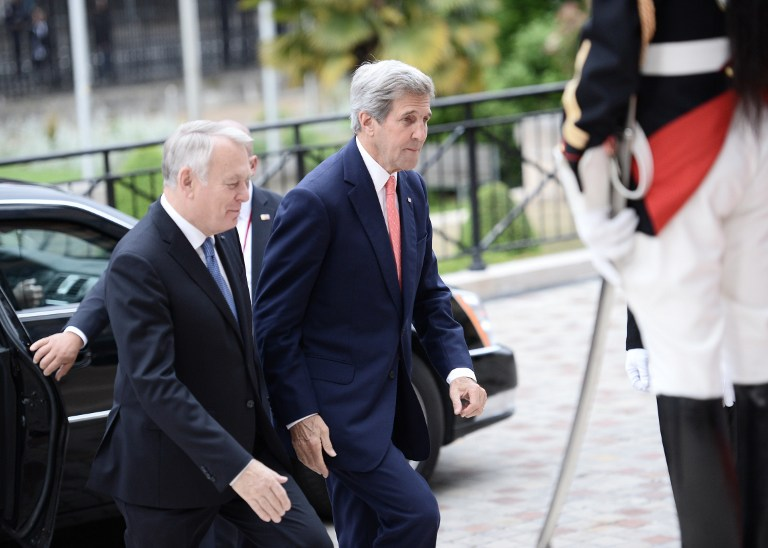 French Foreign Minister Jean-Marc Ayrault (L) welcomes US Secretary of State John Kerry upon his arrival for an international and interministerial meeting in a bid to revive the Israeli-Palestinian peace process, in Paris, on June 3, 2016. (AFP PHOTO / POOL / STEPHANE DE SAKUTIN)