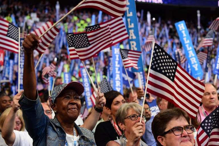 Delegates wave flags as Democratic presidential nominee Hillary Clinton addresses delegates on the fourth and final night of the Democratic National Convention at Wells Fargo Center on July 28, 2016 in Philadelphia, Pennsylvania. (AFP PHOTO/Robyn Beck)