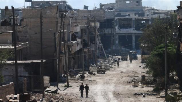 Des combattants syriens pro-régime dans les rues de Ramussa, après leur prise de contrôle d'un district stratégiquement important dans la banlieue d'Alep la veille, le 9 septembre 2016. (Crédit : AFP/George Ourfalian)