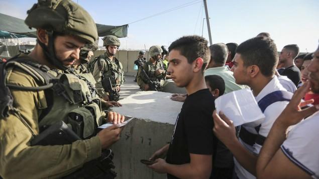 Des soldats israéliens en train de contrôler l'identité palestiniens au checkpoint de Qalandia entre la ville de Ramallah en Cisjordanie et Jérusalem, le 1er juillet 2016 (Crédit : Flash90)
