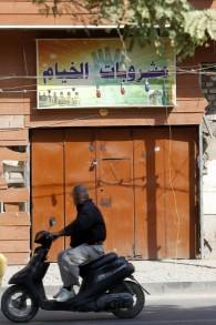 Un Irakien passe devant un magasin d'alcool fermé à Bagdad, le 23 octobre 2016. (Crédit : AFP/Sabah Arar)