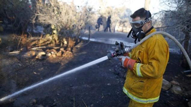 Des pompiers israéliens luttent contre les flammes à Beit Meir, près de Jérusalem, le 25 novembre 2016. (Crédit : AFP/Ahmad Gharabli)