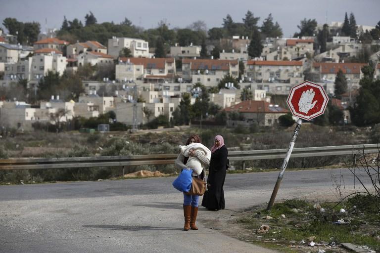 Des Palestiniennes du camp de réfugiés de Jalazoun, près de Ramallah, en Cisjordanie, avec en fond l'implantation israélienne de Beit El, le 25 janvier 2017. (Crédit : Abbas Momani/AFP)
