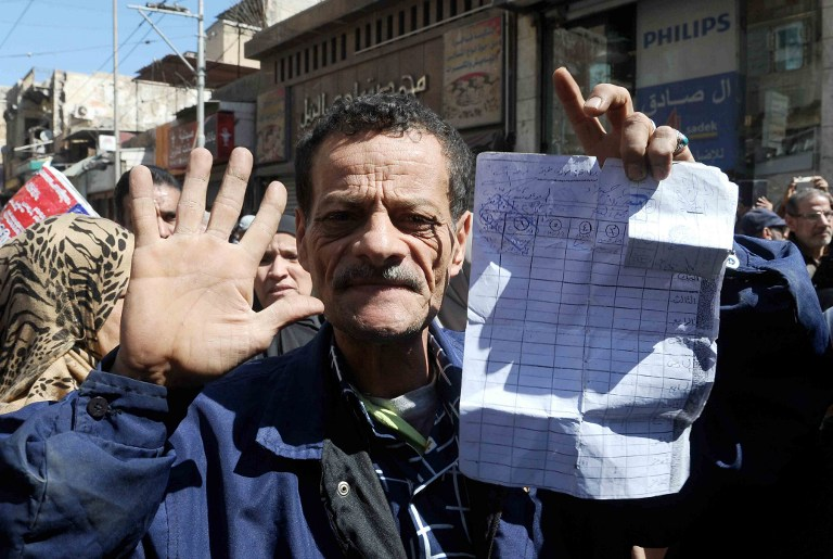 An Egyptian man shows a paper documents as dozens of Egyptians take part in demonstration in front of a government office in downtown Alexandria on March 7, 2017, against the decision of the supply ministry to limit the distribution of subsidized bread to holders of a new system of digital cards issued by the ministry. (AFP PHOTO / STR)