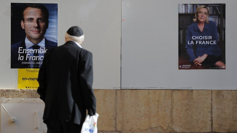 A Jewish man looks at election posters outside the French consulate in Jerusalem, on May 7, 2017 during the second round of the French presidential vote. (AFP Photo/Thomas Coex)