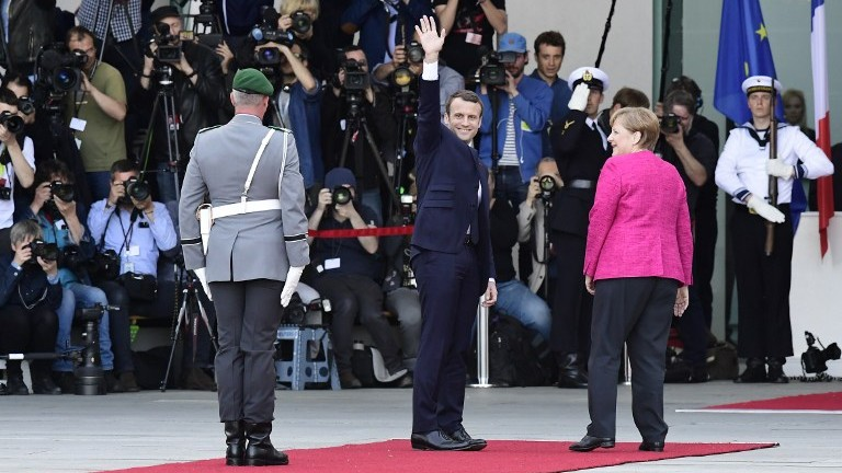 German Chancellor Angela Merkel and French President Emmanuel Macron wave outside of the chancellery in Berlin on May 15, 2017. (AFP Photo/Tobias Schwarz)