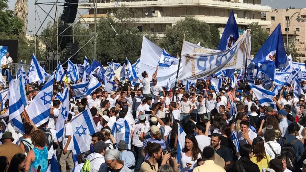 Hundreds of revelers wave Israeli flags as they they prepare to march their way through the city towards the Western Wall for Jerusalem Day. (Like Tress/Times of Israel)